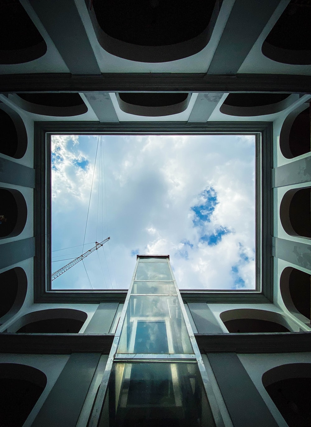 low-angle photography of white and gray building under white and blue skies during daytime