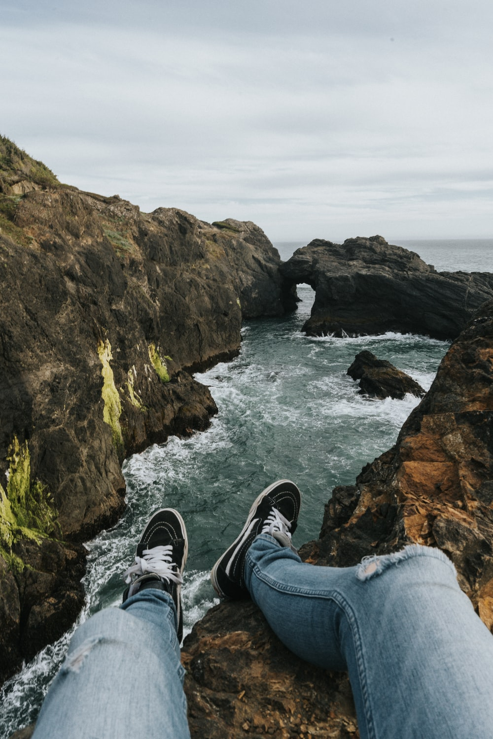 sitting person wearing gray denim distressed jeans on cliff