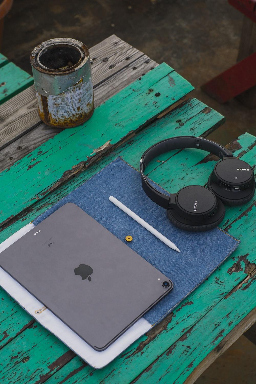 black cordless headphones beside iPad on green table