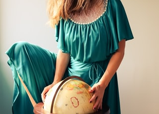 woman standing beside terrestrial globe