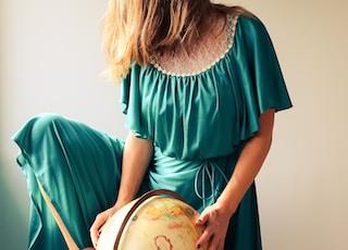 woman standing beside terrestrial globe