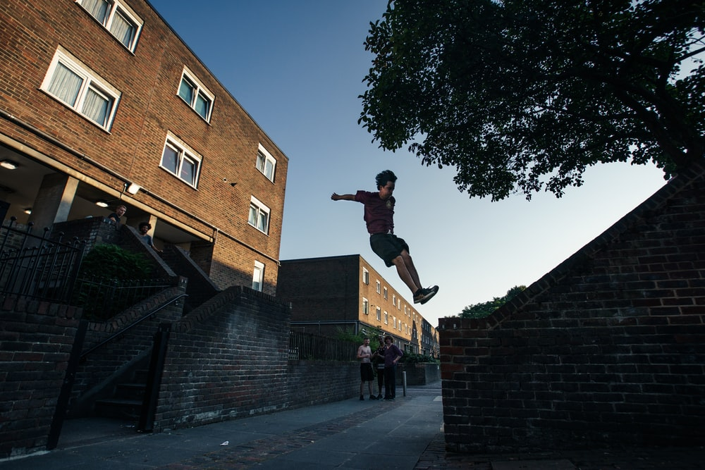 person jumping to brick wall