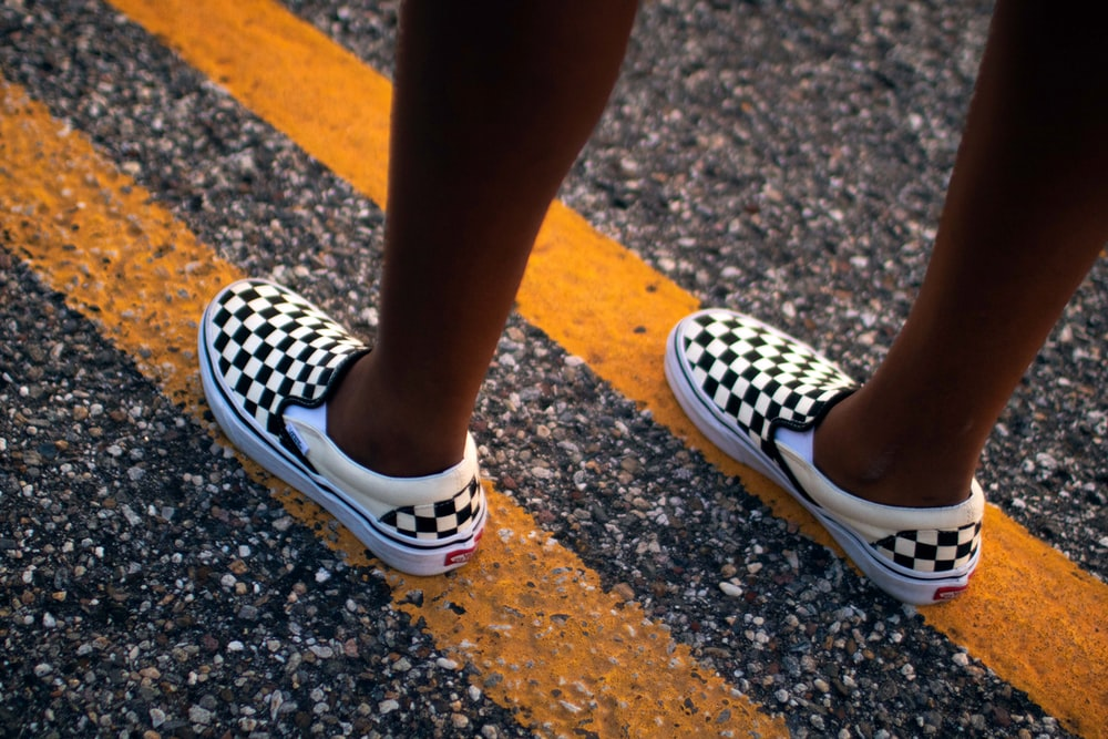 pair of white-and-black Vans checkered slip-on shoes