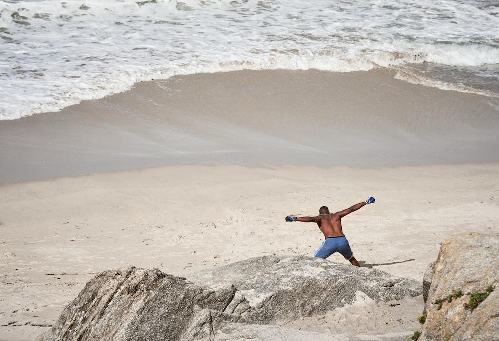 man wearing blue board short walking on seashore