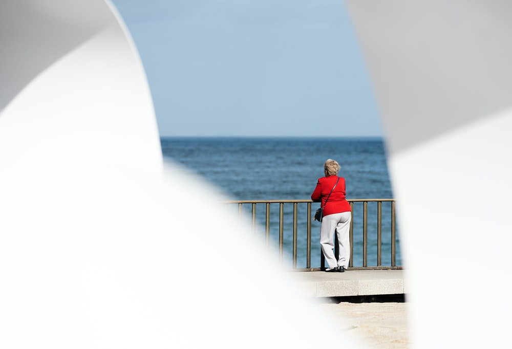 woman in red long-sleeved shirt watching the body of water
