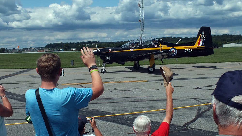 people waving across yellow and black airplane