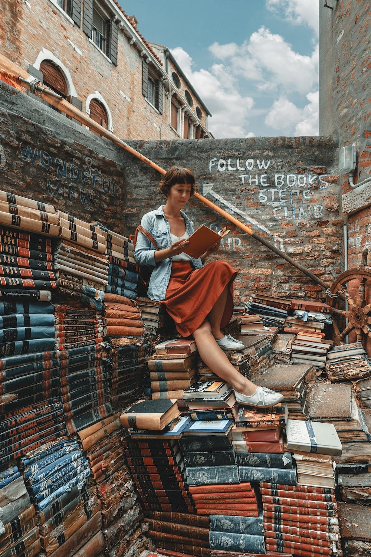 woman wearing denim jacket reading book