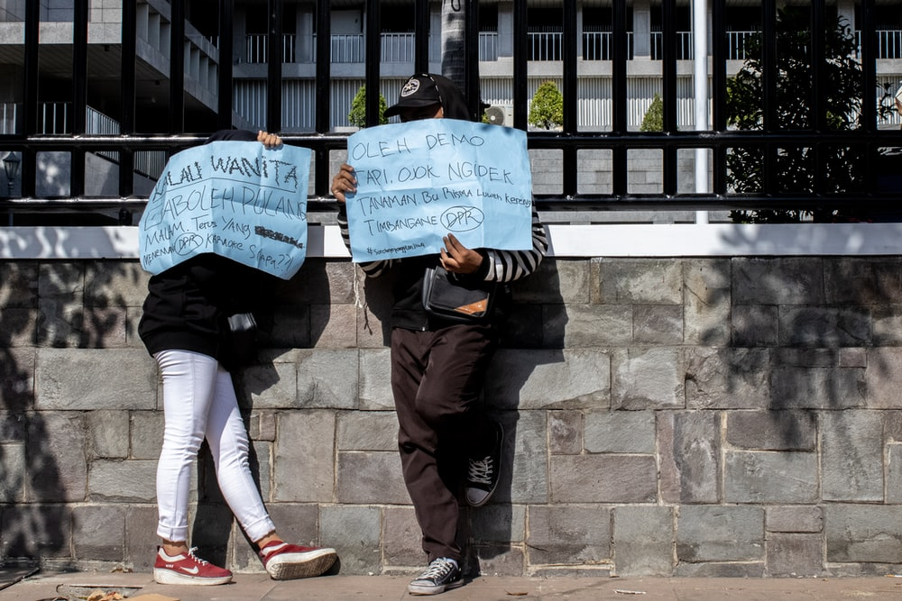 two person holding blue printed signages