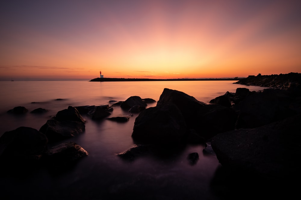 silhouette of rock on body of water during sunset