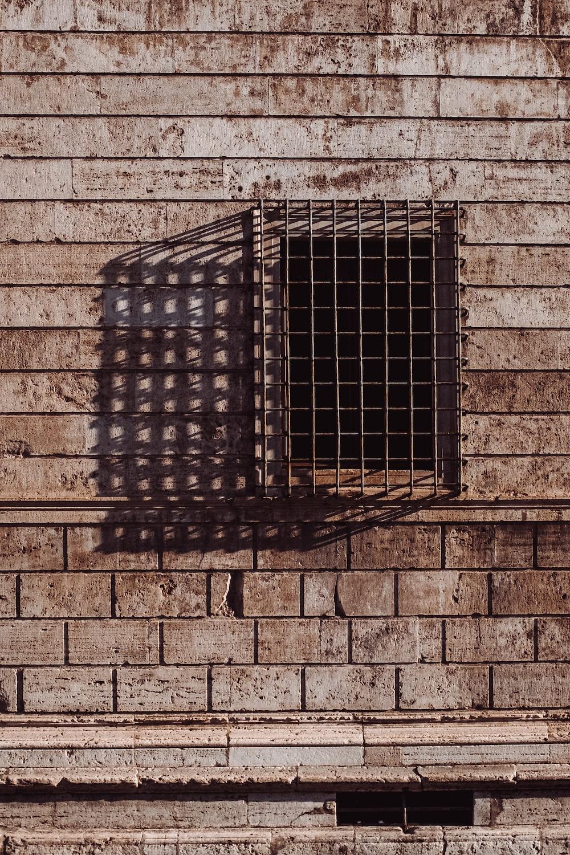 brown metal window frame and brick wall