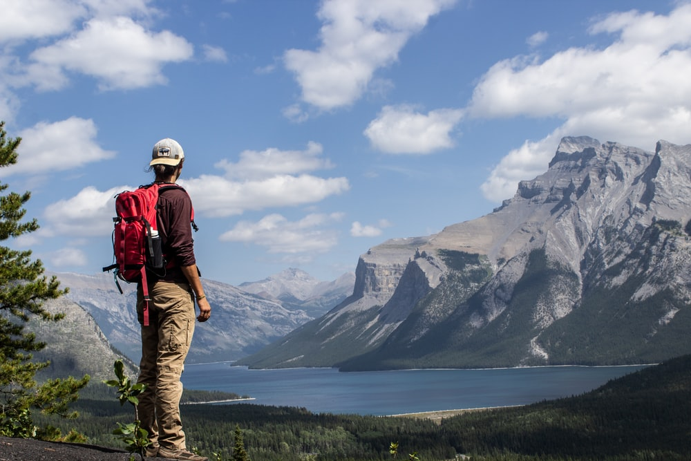 person wearing red backpack standing in front of body of water and mountains during daytime