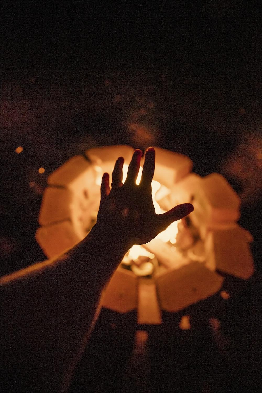 person putting left hand near bonfire