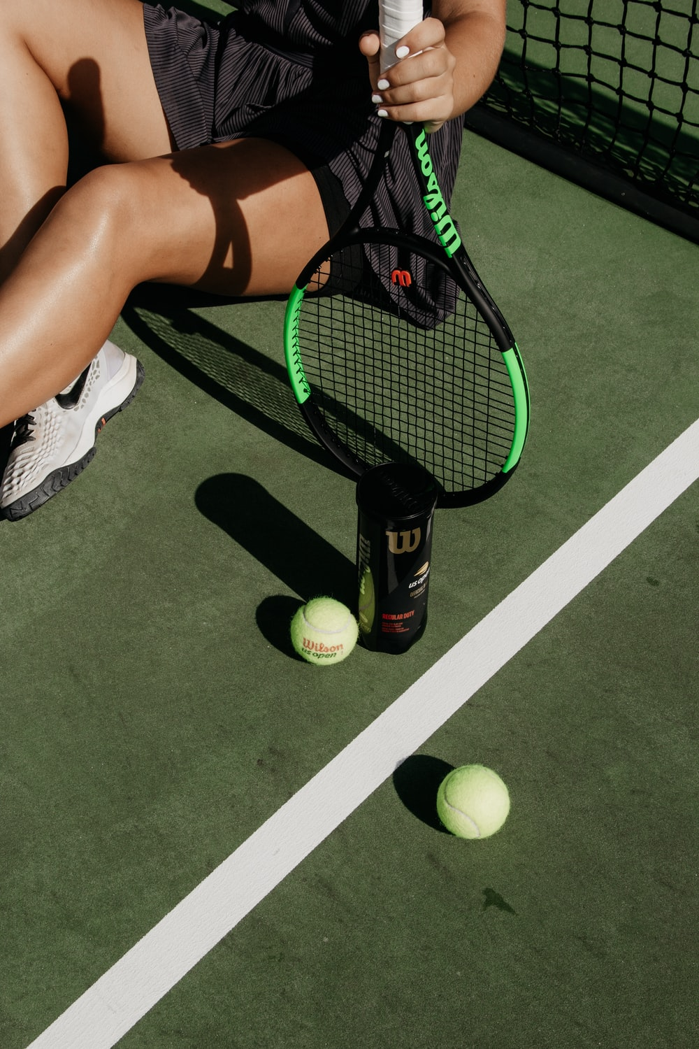 woman sitting while holding tennis racket beside balls