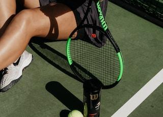 woman sitting while holding tennis racket beside balls