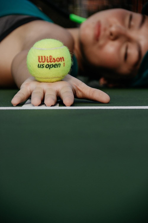 woman lying on tennis court holding green Wilson ball