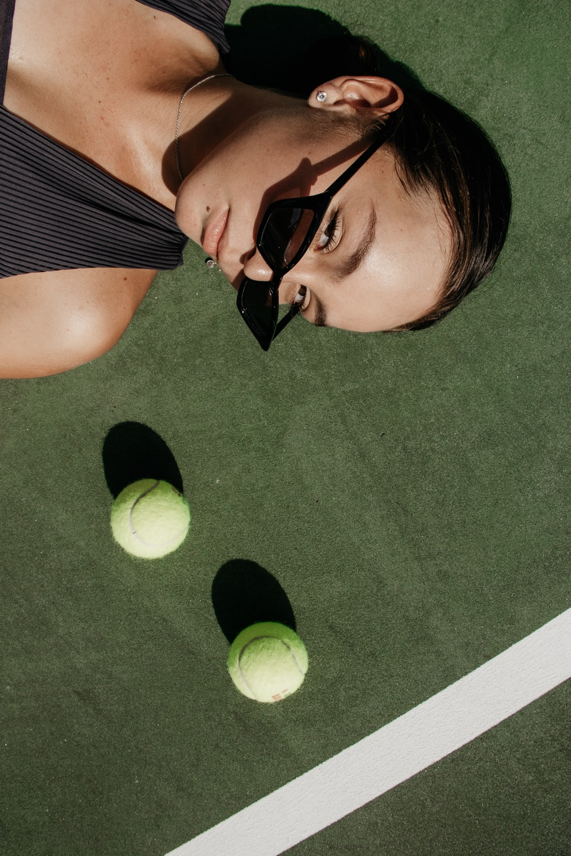 woman lying beside two green tennis balls