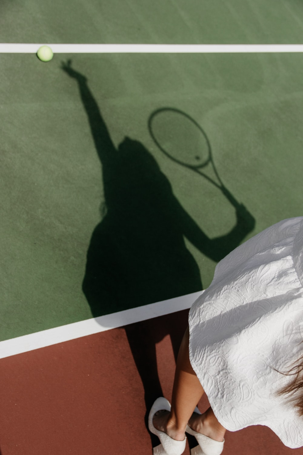 shadow of woman playing tennis on court