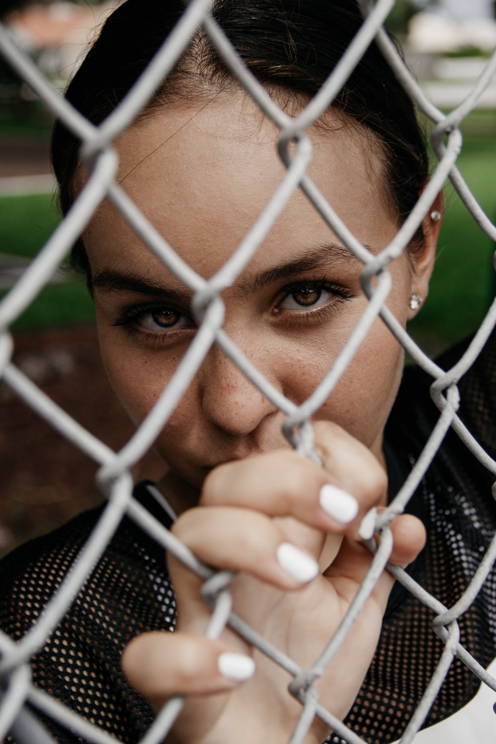 woman holding on iron wire fence