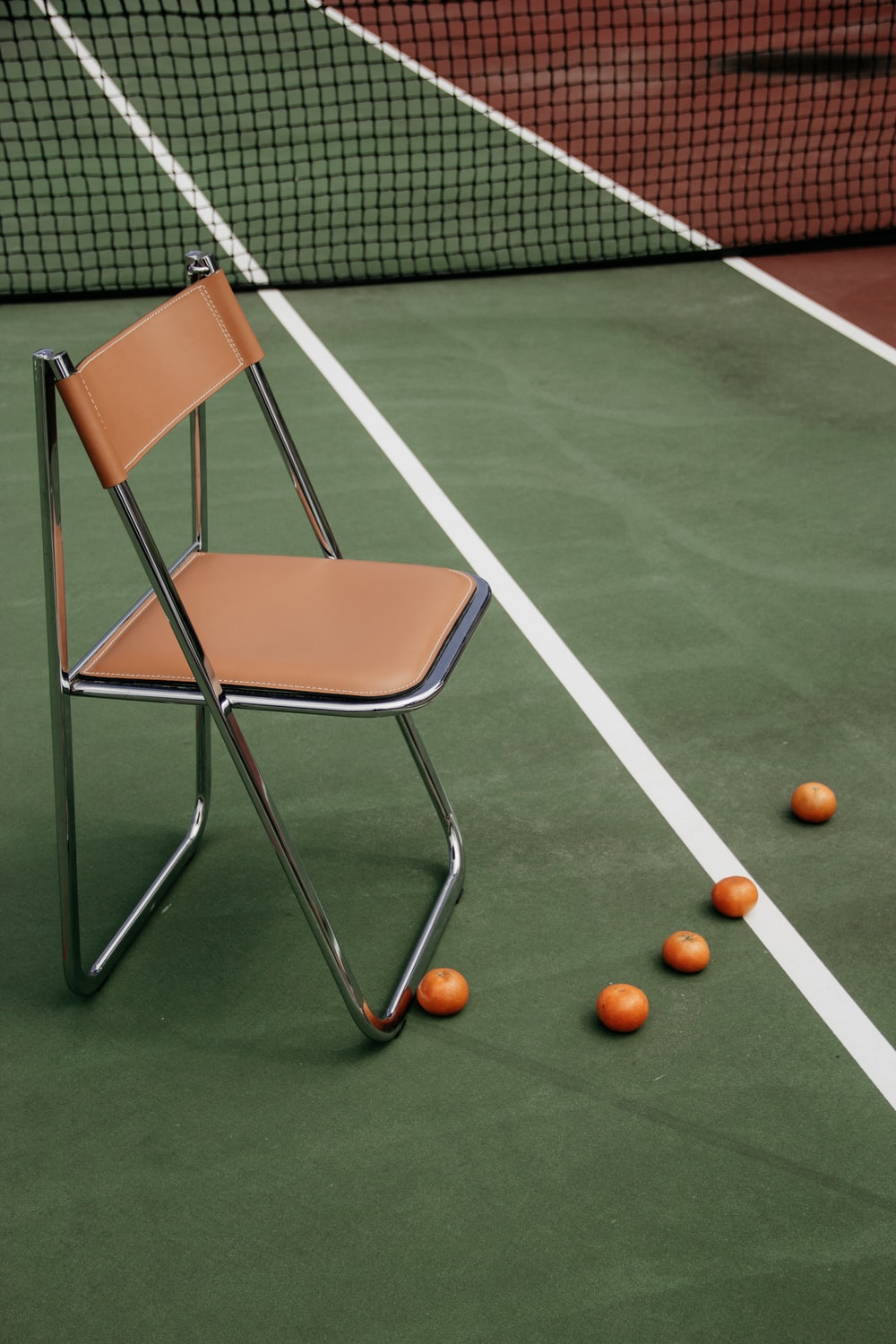 brown leather padded armless chair on tennis court