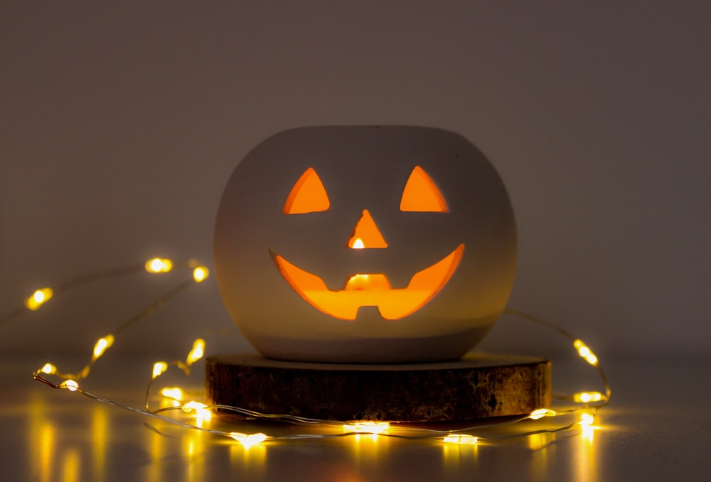 white and orange Jack-O-Lantern near yellow string lights