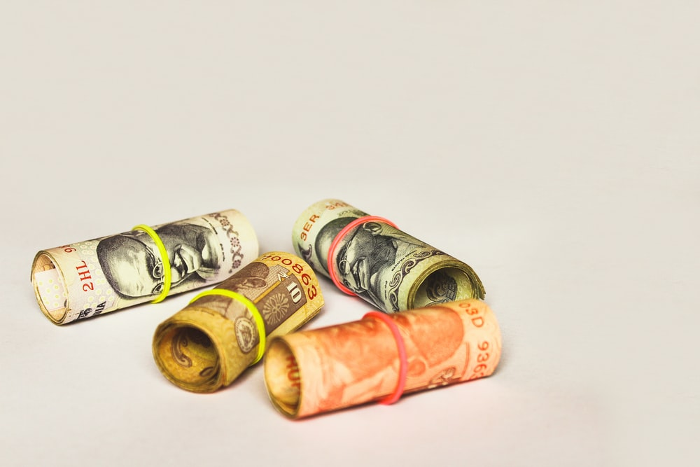 rolled four Indian rupee banknotes