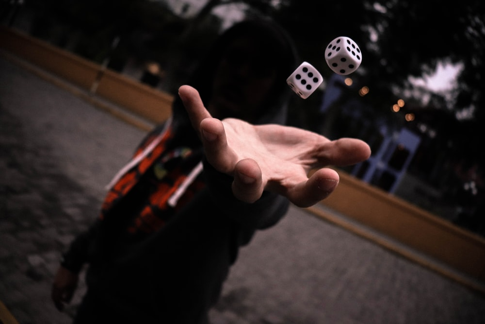 left human hand playing with dice