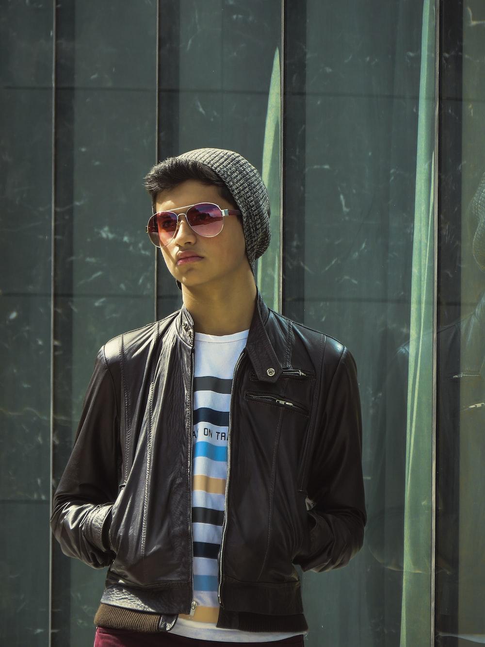 man wearing black leather jacket standing near green wall