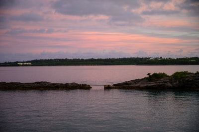 brown wooden dock on body of water during sunset bermuda zoom background