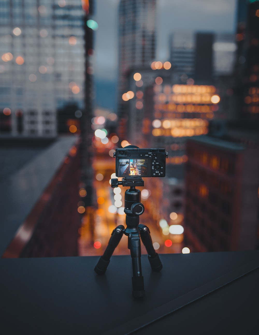 camera on tripod on building roof ledge at the city during night