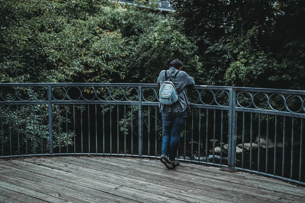 man wearing blue denim jacket and backpack