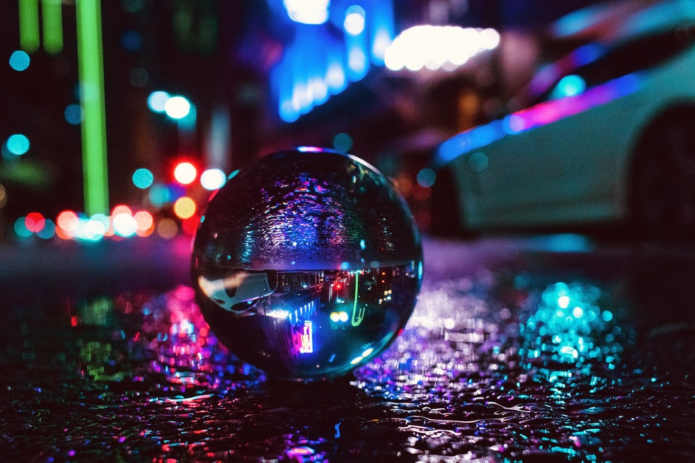 glass ball photography on ground near vehicle with lights during nighttime