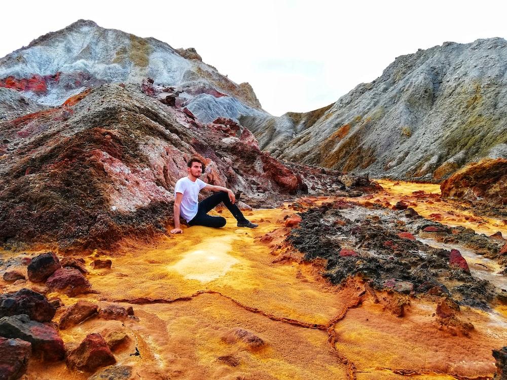 man sitting beside rock formations