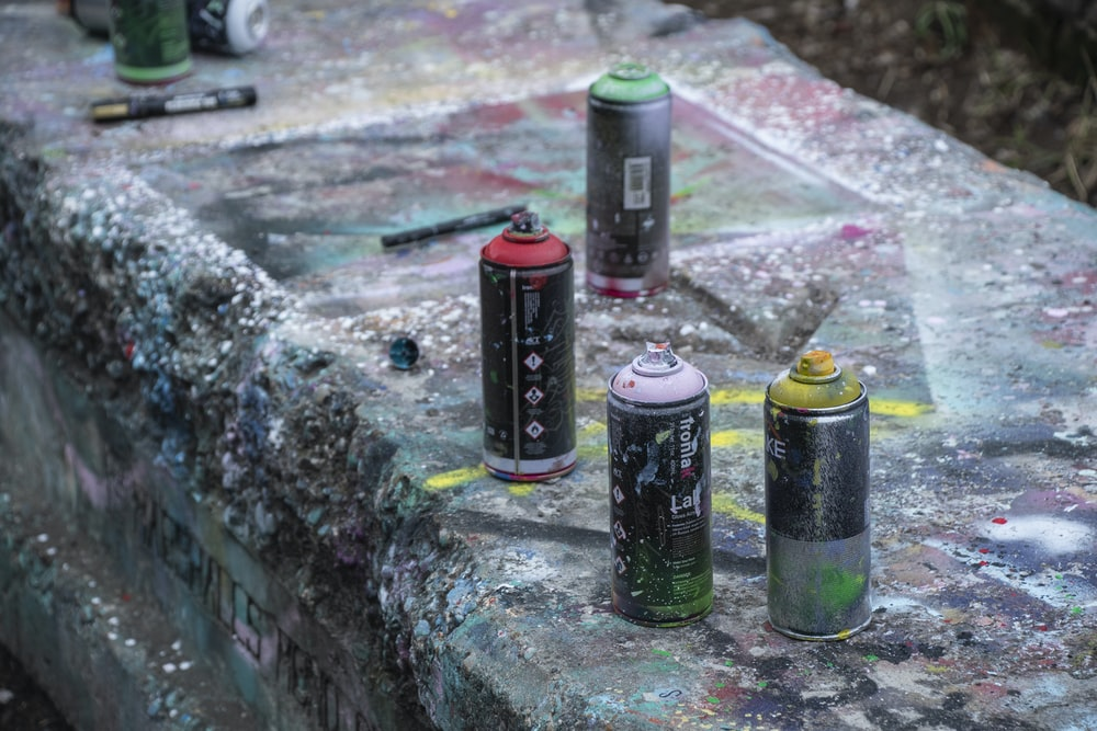 four assorted-colored spray cans