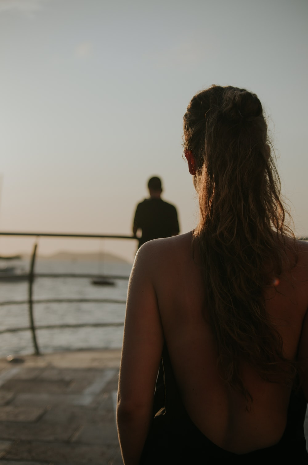 selective focus photography of woman facing on body of water