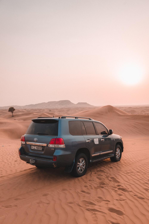 blue SUV on desert ]