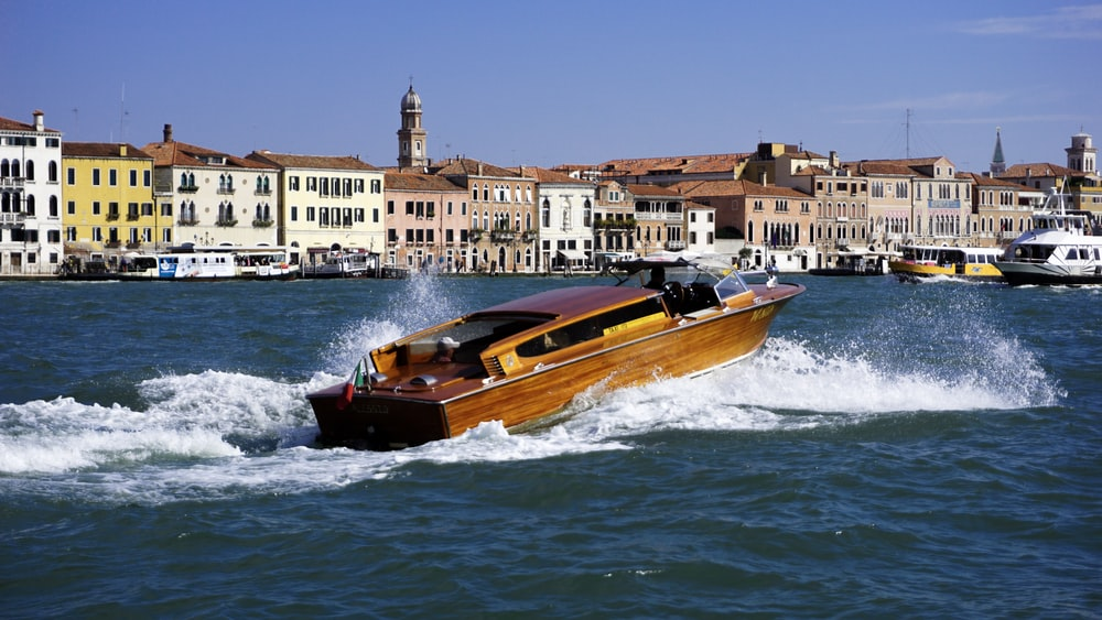 brown boat on sea heading towards city