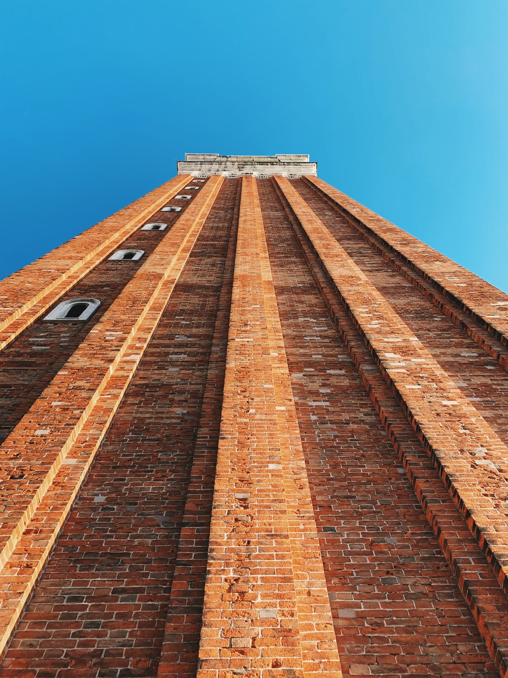 low angle photography of brown brick building under clear sky