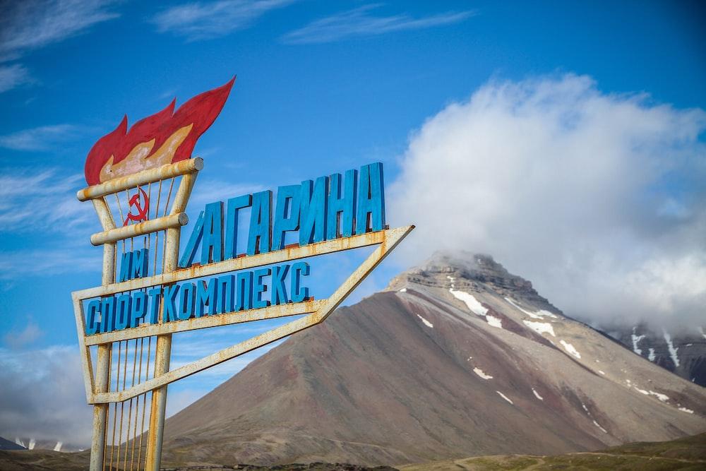 blue signage near mountain