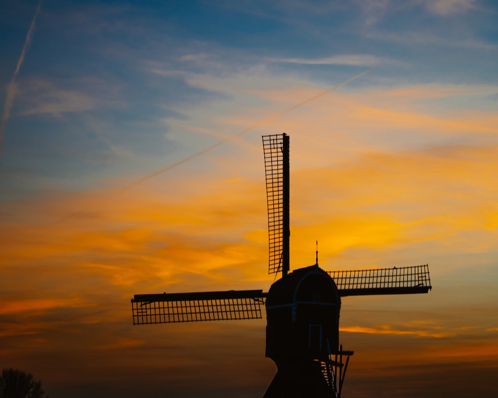 silhouette photography of windmill under golden hour