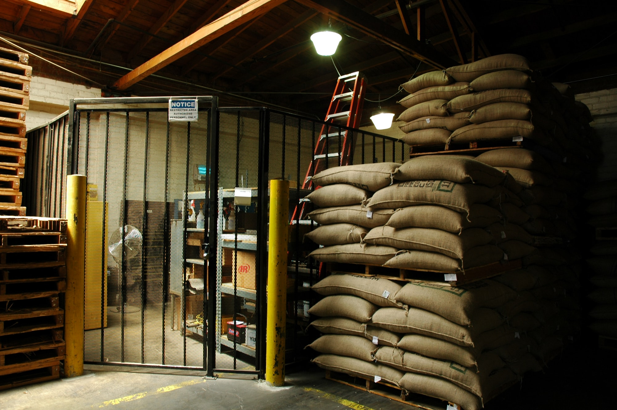 Coffee processor and manufacturing storage of coffee beans arriving from tropical locations around the world, burlap bags, wood crates, secure areas, ladders, yellow bollards, Los Angeles, California, USA