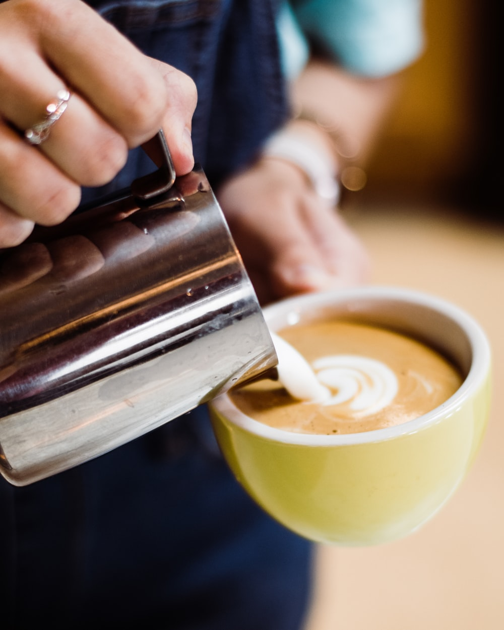 person pouring milk in cappuccino