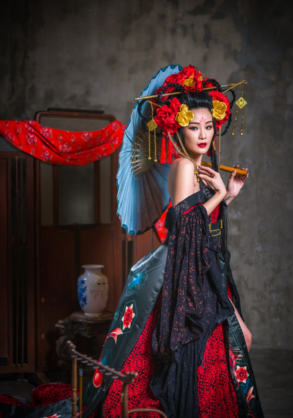 woman in black dress beside wall