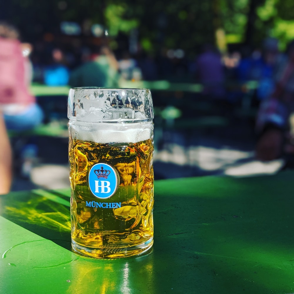 near full Munchen drinking glass on green surface