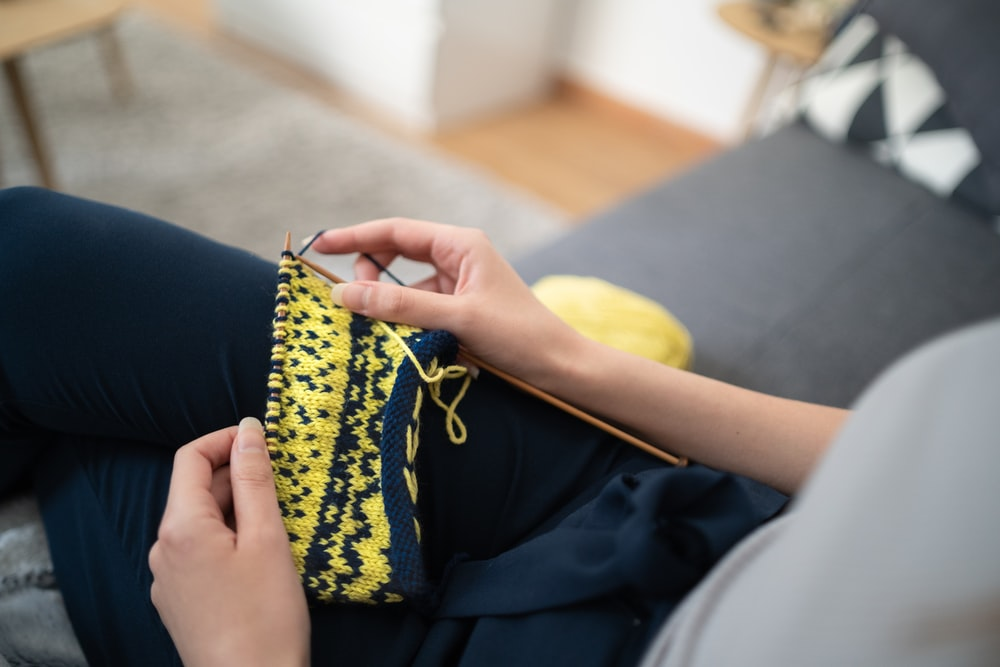 sitting woman knitting yellow and blue textile