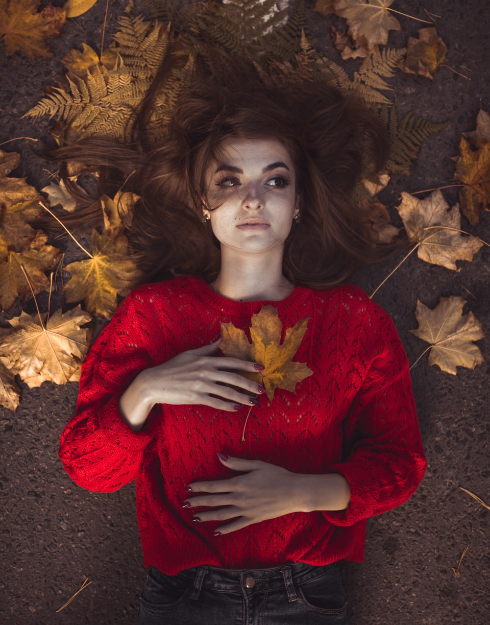 woman wearing red sweater lying besides dried leaves