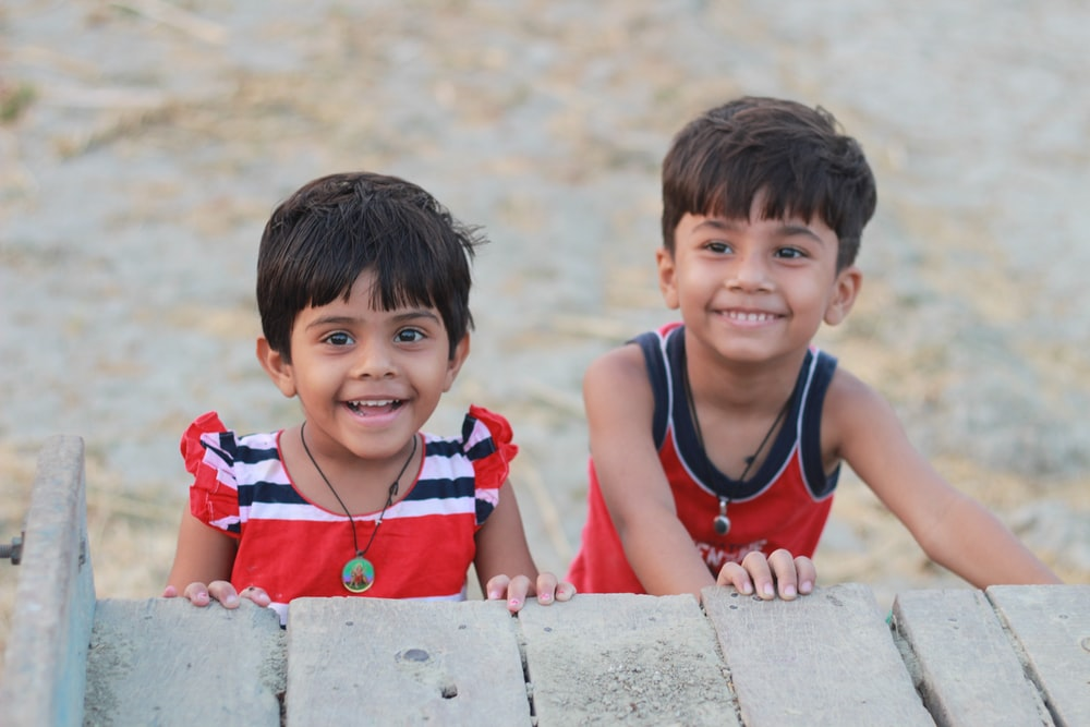 shallow focus photo of girl and boy smiling