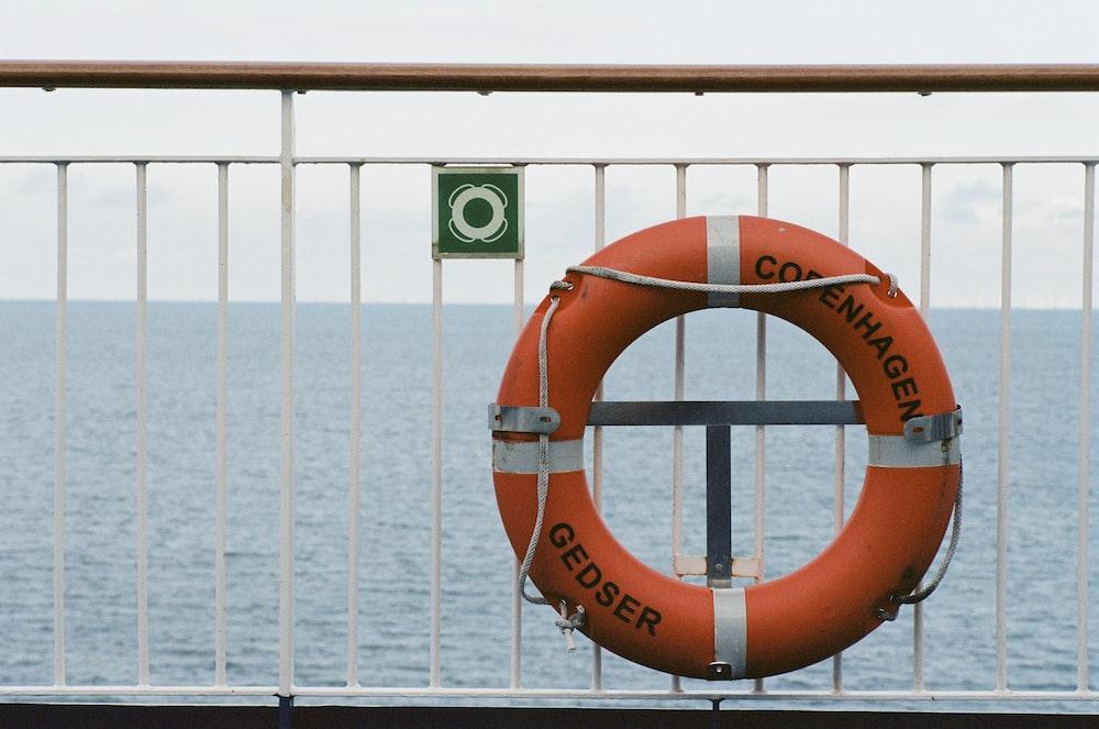 orange and white Copenhagen swim ring near wall