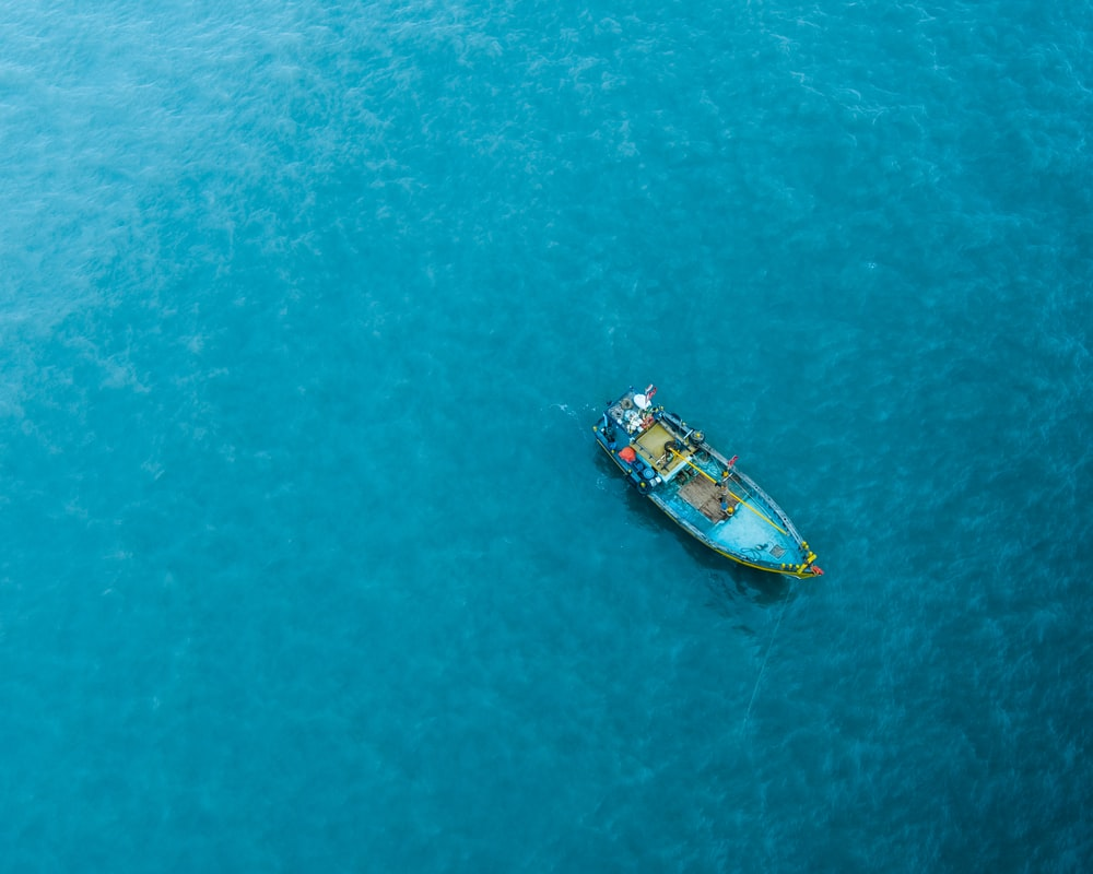 blue canoe boat in the middle of ocean