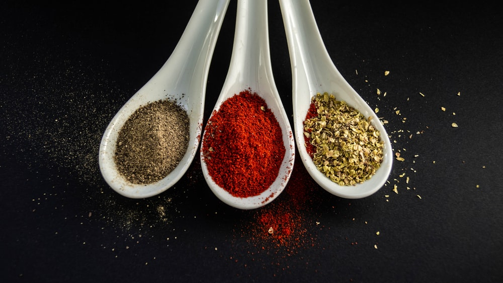 three assorted spices in white spoons