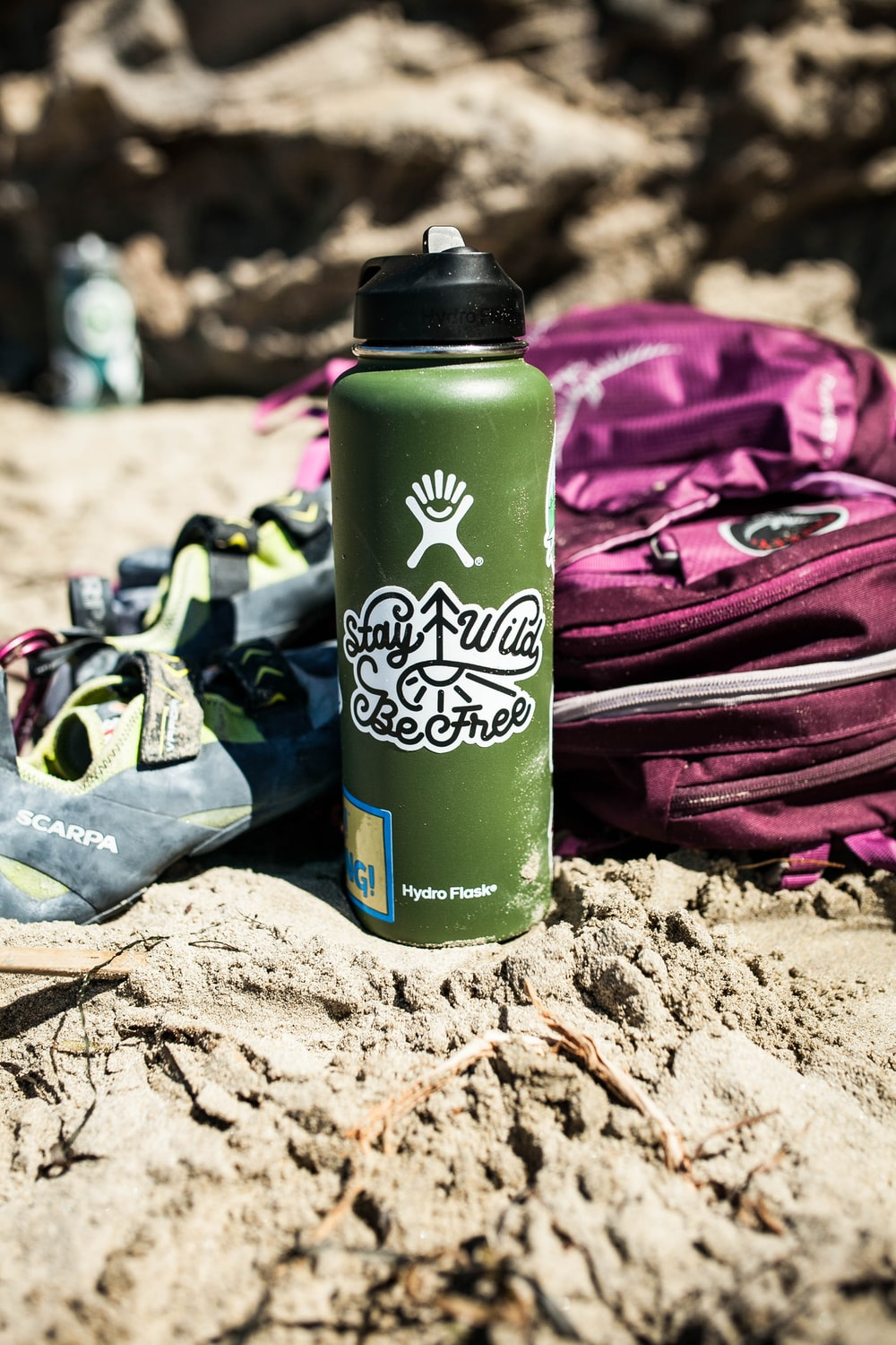 green stainless steel water tumbler besides pink backpack